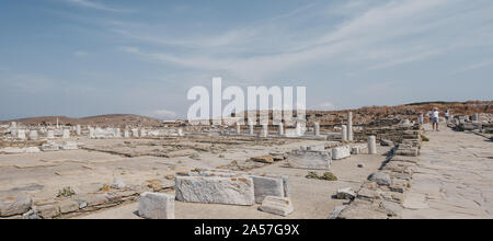Delos, Greece - September 20. 2019: Ruins of agora on the historic island of Delos, Greece, Archaeological Museum of Delos on the background. People w - Stock Photo