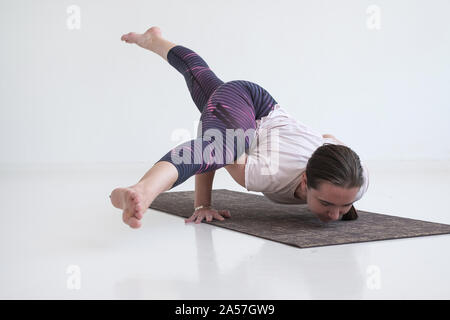 practicing yoga, doing Eka Pada Koundinyasana 2, arm balance twisted pose. - Stock Photo