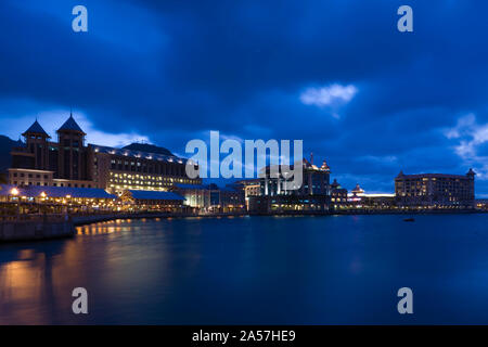 Buildings at the waterfront lit up at dusk, Caudan Waterfront, Port Louis, Mauritius - Stock Photo