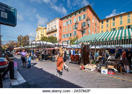 Tourists and local French enjoy a summer day in the outdoor Cours Saleya flea market marketplace in Old Town Nice France on the Riviera - Stock Photo