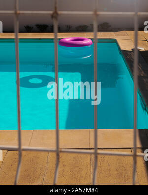 A pink inflatable ring floats on a clear blue swimming pool in Olhos D'Agua, Portugal on a warm summer day - Stock Photo