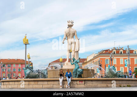Two women relax in front of the Apollo Statue at the Fountain of the Sun in Place Massena, in the city of Nice France, on the French Riviera. - Stock Photo