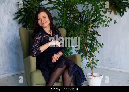 Portrait of a beautiful Asian woman sitting in a green chair