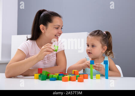 Smiling Daycare Worker Playing With Child Stacking Building Blocks On White Desk - Stock Photo