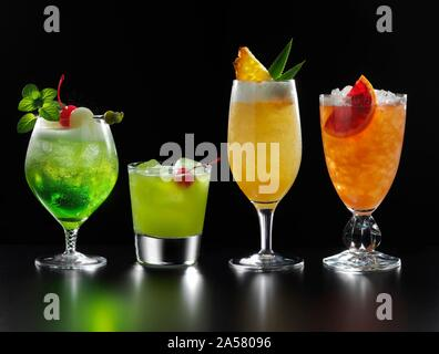 Four different fruity cocktails, black background, Germany - Stock Photo