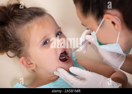Close-up Of A Female Dentist With Mirror Examines Teeth Of Little Anxious Girl - Stock Photo