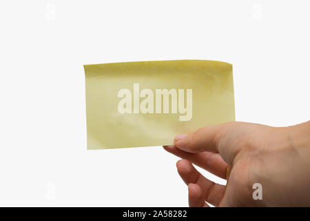 Woman holding a blank yellow sticky note isolated on white background, space for text - Stock Photo