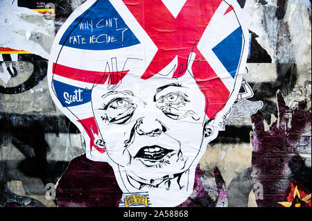 A sticker of Theresa May is seen on a wall.As the Brexit deadline looms, new murals and paste-ups appear on the streets of London. Brick Lane, in London's east end, is one of the most popular places to find all kind of art around the Brexit. Also in the famous district of Shoreditch, tourists walk and take photos around this political street art. - Stock Photo