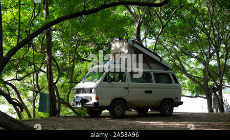 Camper van parked by the beach with tropical vegetation , side view, at Concha lbeach, Costa Rica - June 25th, 2018. - Stock Photo