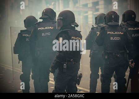 Barcelona, Spain. 18 October, 2019:  Spanish National riot agents are covered in smoke during a protest against the Supreme Court's verdict against 12 Catalan leaders for sedition and misuse of public funds in relation with a banned referendum on secession and an independence vote at the Catalan Parliament in October 2017. - Stock Photo