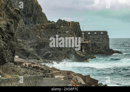 Vallehermoso beach in La Gomera with Huge waves crashing on basalt rocks. Old stone building named El Castillo del Mar, an old banana factory. Shot by - Stock Photo