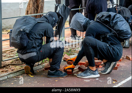 Hong Kong protestors dig up the pavement for ammunition to throw at the police - Stock Photo