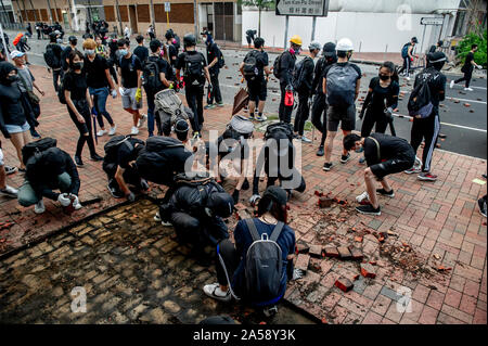 Hong Kong protestors on the streets of Hong Kong barricade against the police and throw broken bricks dug from the pavement - Stock Photo