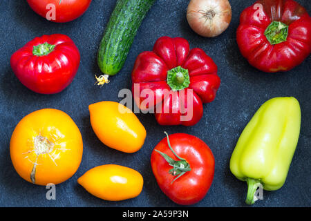 Fresh whole vegetables from new harvest on dark blue background. Washed pepper, tomatoes, onion and cucumber on table. Top view. Close-up. Raw foods - Stock Photo