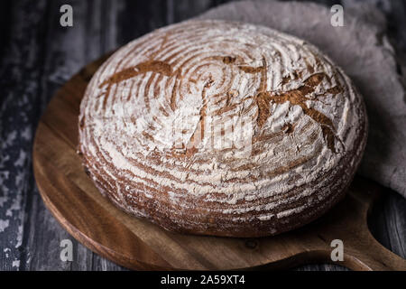 A homemade sourdough levain bread with rye and wheat flour. The bread is on a round cutting board on a dark wooden table. There is a brown soft linen
