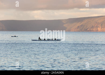 Outrigger canoe off Wailea beach walk in south Maui with Molokini Crater in the background - Stock Photo