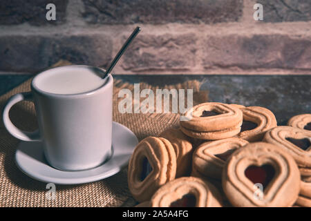 cup of milk on a rag next to some tasty cookies. food concept - Stock Photo