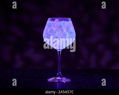 Gin tonic under blacklight (UV) illumination. Glow in the dark drink. - Stock Photo