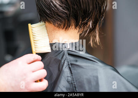 Hairdresser shakes cut hair from neck of woman at hair salon. Barber Man is cleaning cut hair from neck of woman in beauty salon. Haircut at salon.