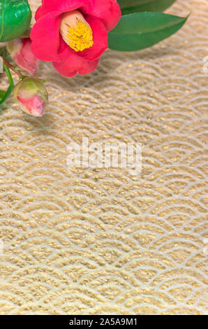 A Japanese greeting card with Tsubaki flower also called the winter rose on a traditional lace circles motif pattern on a golden paper background. - Stock Photo