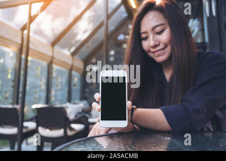 Mockup image of a beautiful asian woman holding and showing white mobile phone with blank black screen in cafe - Stock Photo