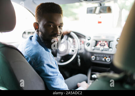 happy young african american man driving a car