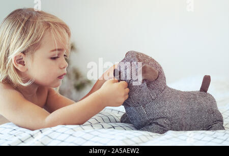 Portrait of a cute little baby boy having fun with his little friend, soft toy doggy, with pleasure spending time at home, preparing to nap - Stock Photo