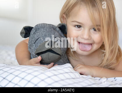 Baby having fun at home, closeup portrait of a cute little boy making faces, showing the tongue, playing with soft toy dog, happy healthy childhood - Stock Photo