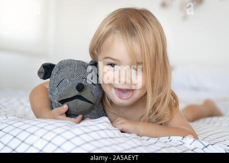 Portrait of a happy little baby boy having fun at home, lying down on the bed with favourite soft toy and making faces, enjoying childhood - Stock Photo