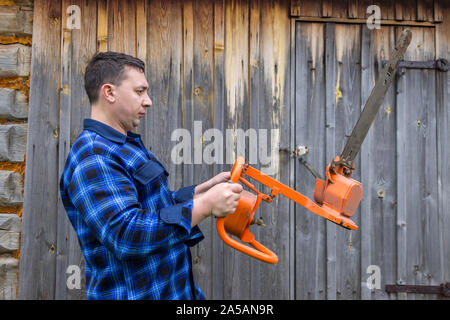 A man works with a chainsaw in his farm on the background of an old wooden barn - Stock Photo