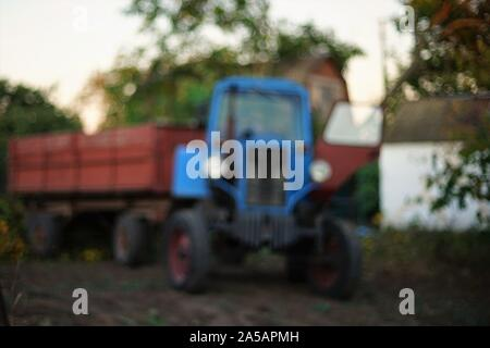 Blue tractor with trailer stands on a farm village, rural landscape - Stock Photo