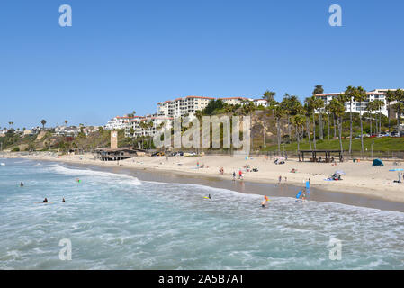 SAN CLEMENTE, CALIFORNIA - 18 OCT 2019: The beach and coastline with surfers and sunbathers seen from the pier in the South Orange County beach town. - Stock Photo