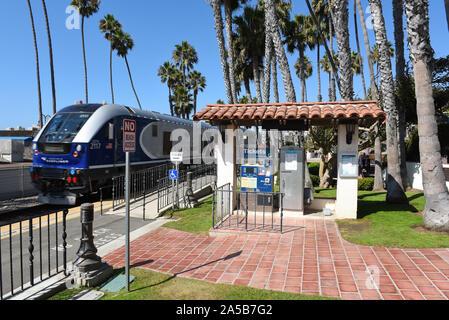 SAN CLEMENTE, CALIFORNIA - 18 OCT 2019: Ticket Kiosk at the Sancelmente Pier as a Metrolink Pacific Surfliner train speeds through. - Stock Photo