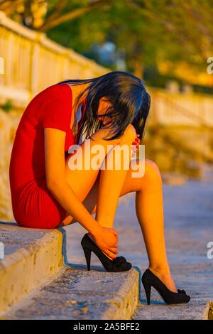 Deeply-upset teenager girl sitting on waterfront lit by intensive hot warm sunset light outdoors sideview side-view leggy legs leg - Stock Photo