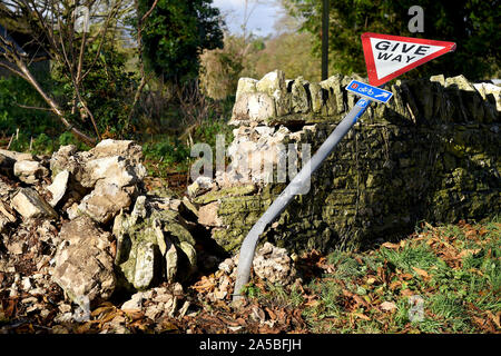 Give Way sign and wall that has been knocked down, England - Stock Photo