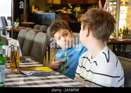 Two boys waiting for pizza in a restaurant.  - brothers having fun. - Stock Photo