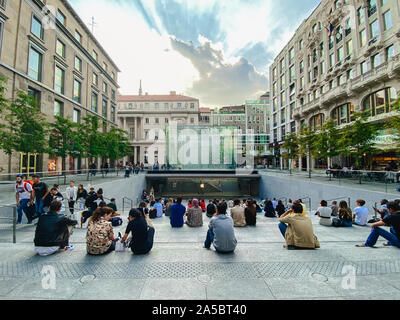 September 25, 2019 Italy. Milan. A lot of people are sitting on steps near apple store in Milan. On staircase, admiring the crystal parallelepiped of - Stock Photo