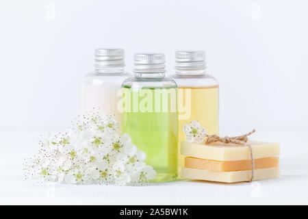 natural cosmetic bottles and handmade soap bar with fresh flowers, closeup - Stock Photo