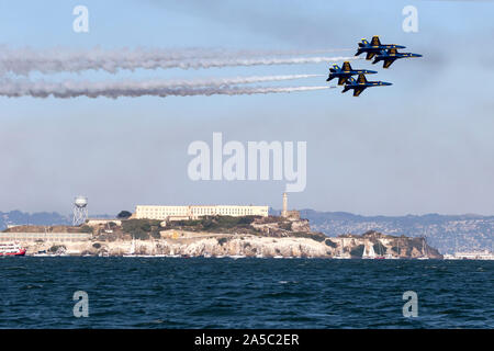 Blue Angels F-18 Hornets in diamond formation pass over Alcatraz during a 2019 San Francisco Fleet Week flight demonstration. - Stock Photo