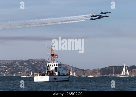 Blue Angels F-18 Hornets in diamond formation pass over the Coast Guard Cutter Pike (WPB-87365) during a 2019 San Francisco Fleet Week flight demonstr - Stock Photo