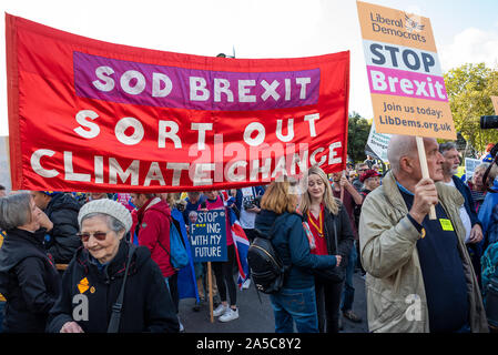 London, UK, 19 Oct 2019. Peoples Vote March. While Parliament debated the deal negotiated by PM Boris Johnson with the EU hundreds of thousands of anti Brexit protestors marched from Park Lane to Parliament Square. Pictured marchers holding raised Sod Brexit Sort out Climate Change banner. Credit: Stephen Bell/Alamy - Stock Photo