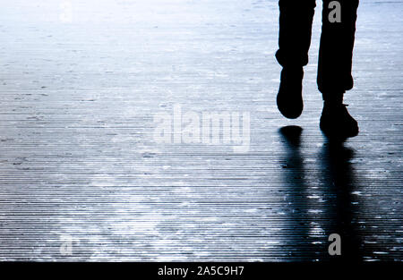 Blurry shadow silhouette of a person walking in the night, detail of legs - Stock Photo