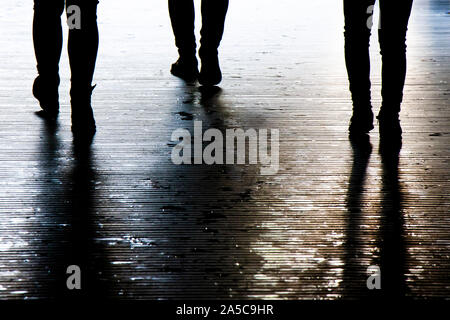 Blurry shadow silhouette of a people walking in the night, detail of legs - Stock Photo