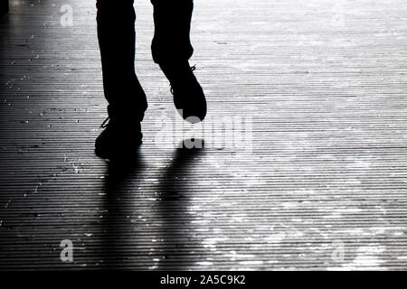 Blurry shadow silhouette of a man walking in the night, detail of legs - Stock Photo