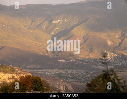 Mountain, misty landscape.In the valley there is a small town, above it rise the mountains covered with forest. - Stock Photo