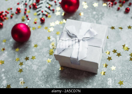 Silver gift with bow on grey snowy background with red Christmas balls and gold confetti stars. - Stock Photo