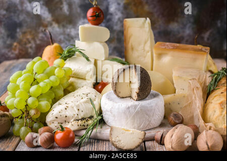 A variety of cheeses, nuts, fruits, spicy herbs and onion baguette on a rustic background. - Stock Photo
