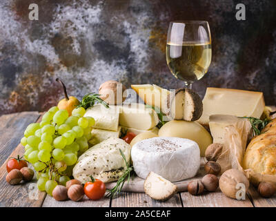 Food still life: Different types delicious cheeses, glass of white wine, nuts, fruits, spicy herbs and onion baguette on a rustic background. - Stock Photo