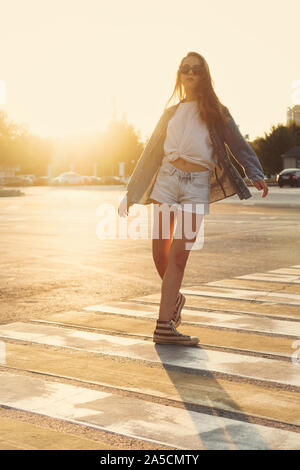 Lovely teenager girl posing at the crosswalk in the sunset. Happy summer, vacation, travel. Summertime. Lifestyle. People, street style and holidays c