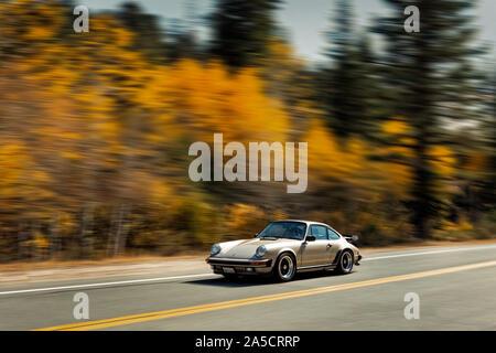 Classic 1980's Porsche 911 driving in the Sierra Nevada California USA - Stock Photo
